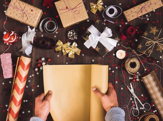 Мужская рука разворачивает рулон оберточной крафт-бумаги для упаковки рождественской подарочной коробки
