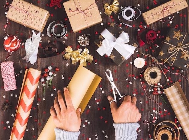 Человек рука держа рулон крафт-оберточной бумаги с ножницами для резки упаковки рождественской подарочной коробке