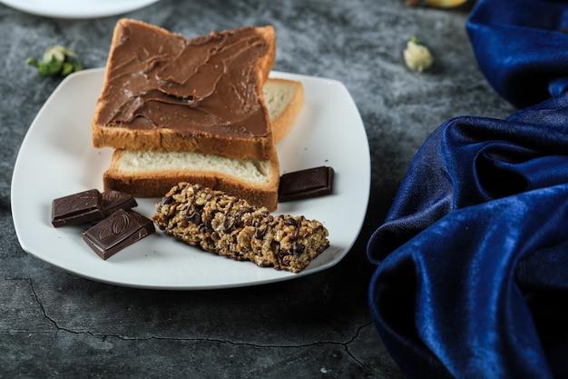 Тост из шоколадного хлеба с кусочками шоколада в белом блюдце
