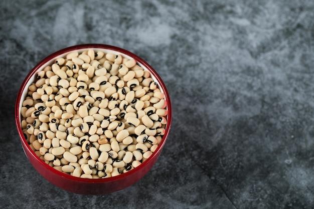 Белые сухие бобы в красной миске