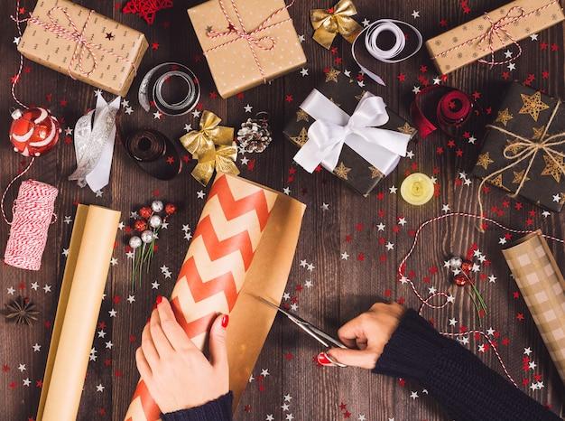 Женщина рука держа рулон крафт-оберточной бумаги с ножницами для резки упаковки рождественской подарочной коробке