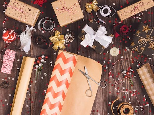 クリスマスのギフト用の箱を切るためのはさみが付いているクラフト包装紙のロール