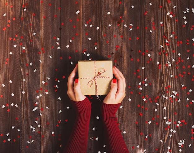 Женщина в руке держит рождественскую подарочную коробку