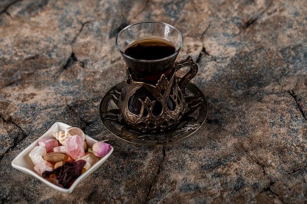 Стакан чая с орехами и сладостями в белом блюдце