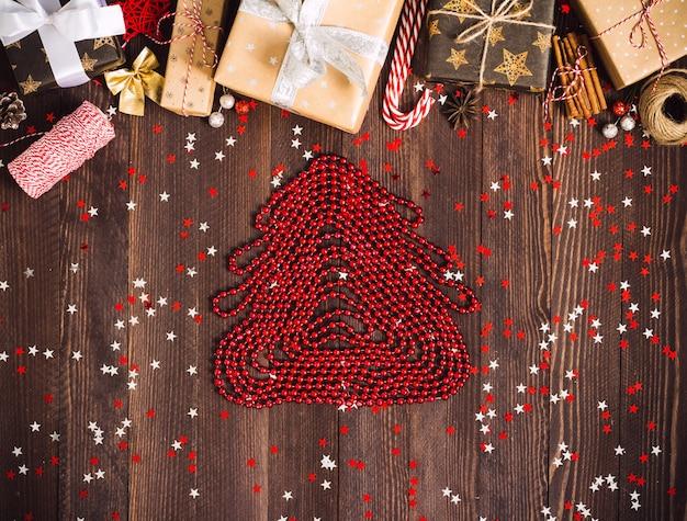 赤いビーズ新年ホリデーギフトボックスから装飾されたお祝いテーブルから作られたクリスマスツリーの図