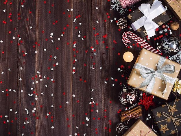 Рождественская подарочная коробка на украшенном праздничном столе с шишками из конфет