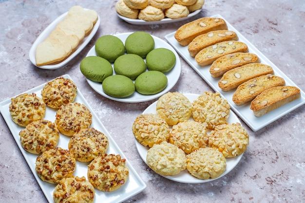 さまざまなナッツクッキークルミクッキー、ピーナッツクッキー、アーモンドクッキー、ライトテーブルの抹茶クッキー