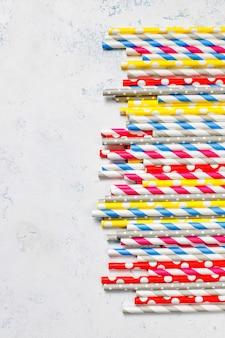 Бумажные соломинки разных цветов на светлом столе с