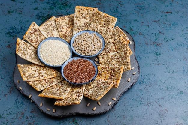 ヒマワリの種、リネンシード、灰色のテーブルにゴマとスナッククッキー