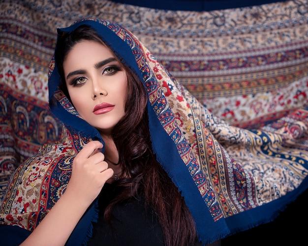 パターンを持つオリエンタルスタイルヒジャーブを宣伝する女性モデル