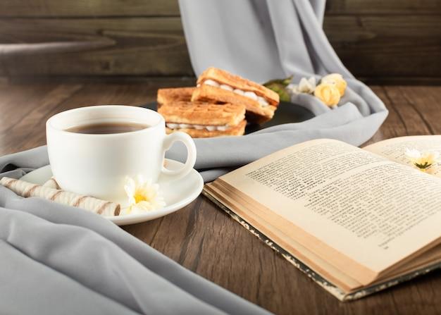 Вафли в черном блюдце, чашка чая на деревянный стол.