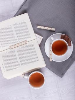 Книга, сладкие закуски и чашка чая на столе