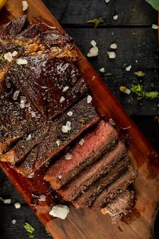 生の肉ステーキをスライスし、塩を加え、黒いテーブルで提供しています