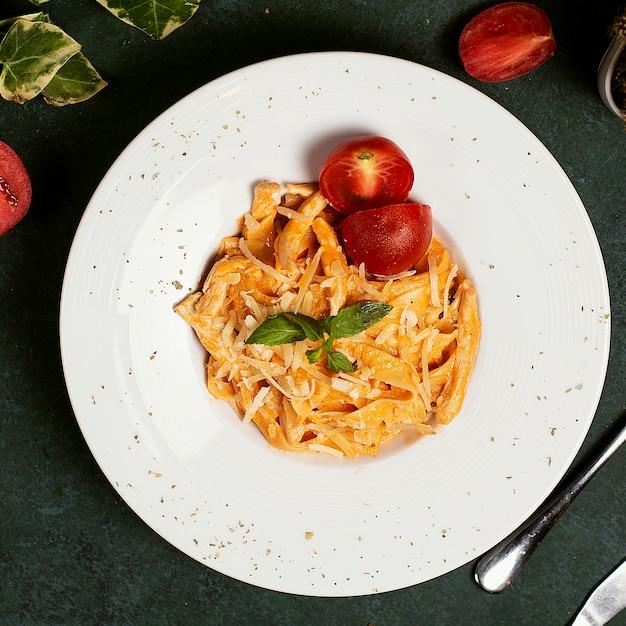 Паста в томатном соусе с нарезанным пармезаном, помидорами и базиликом.