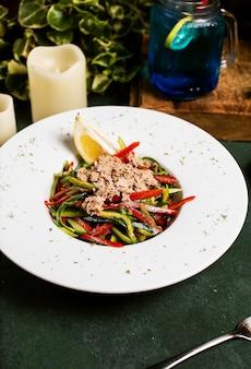 Овощной салат с огурцом, сладким перцем, рубленой курицей и лимоном в оливковом масле.