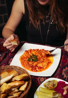 Девушка, клиент ест менемен, турецкий завтрак омлет с луком и помидорами.