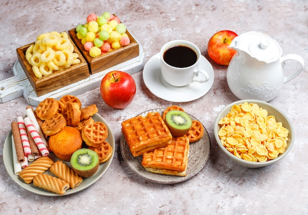 さまざまなお菓子、ウエハース、コーンフレーク、一杯のコーヒー、トップビューで朝食します。