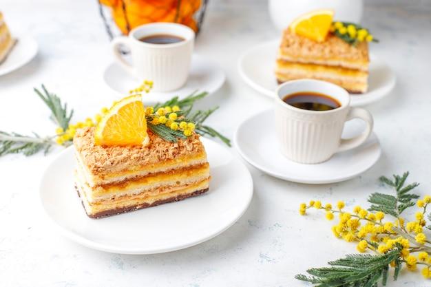 Апельсиновый торт украшен свежими дольками апельсина и цветами мимозы на свете