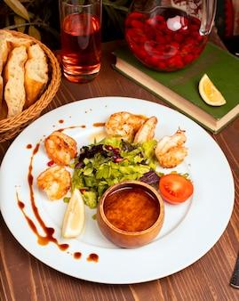 Жареные креветки с зеленым салатом, помидорами, лимоном и соусом в белой тарелке.