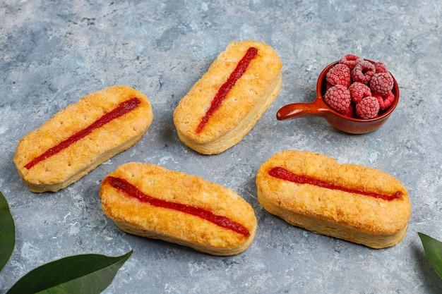 Слоеное печенье с малиновым вареньем и замороженной малиной на свету