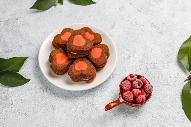 ハート型の明るい背景に冷凍ラズベリーとバレンタインクッキー