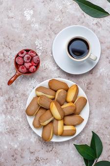 Печенье с начинкой из малинового варенья и замороженной малины на светлом фоне, вид сверху
