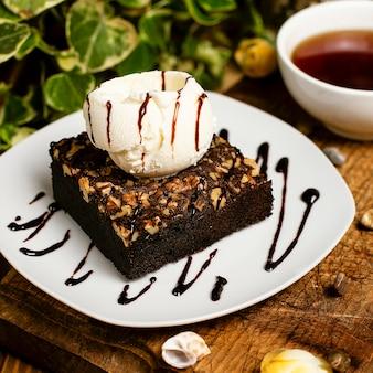 Ломтик шоколадного брауни с грецким орехом и ванильным мороженым.