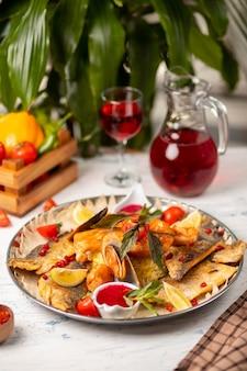 Жареная рыба на гриле и морепродукты подаются с травами, лимоном и соусом из красных помидоров.