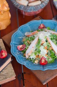 Куриный салат цезарь с нарезанным сыром пармезан, свежим салатом и помидорами, крекеры в синей тарелке.