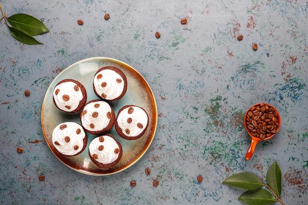 Кофейные кексы украшены взбитыми сливками и кофейными зернами.