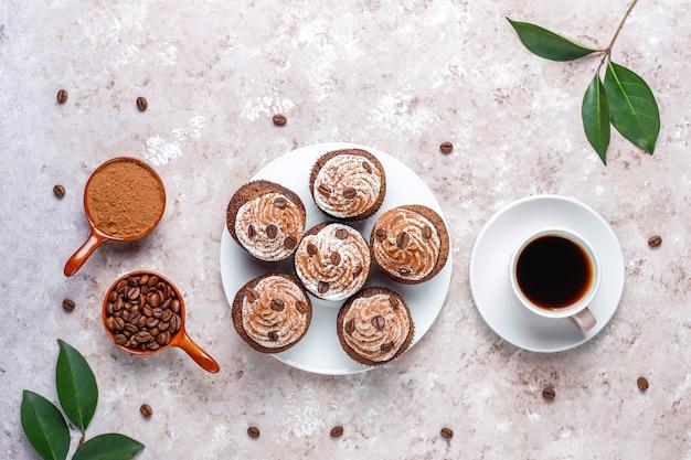 ホイップクリームとコーヒー豆で飾られたコーヒーカップケーキ。