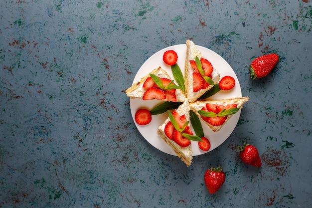 Вкусные домашние кусочки клубничного торта с кремом и свежей клубникой, вид сверху