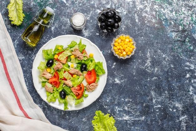レタス、オリーブ、トウモロコシ、トマト、トップビューのツナサラダ