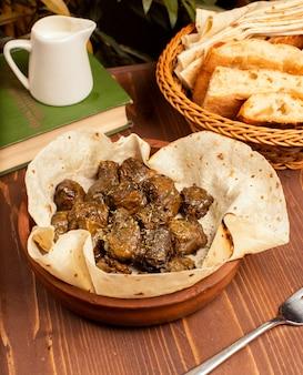 青ぶどうの葉に肉、米、ハーブ、タマネギを詰め、オリーブオイルで調理し、ラバッシュとパンを添えて。