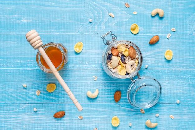 健康的な朝食。新鮮なグラノーラ、ミューズリー、ナッツ、冷凍ベリー。上面図。コピースペース。