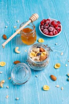 Здоровый завтрак. свежие мюсли, мюсли с орехами и замороженными ягодами. вид сверху. копировать пространство