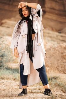 白のトレンチコート、黒のショール、ブルージーンズのファッションモデル