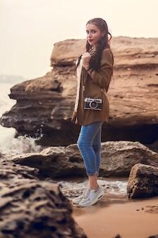 石の上のビーチに女の子が立っています。
