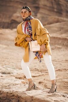 アウトドアでトレンディな黄色のトレンチコートのファッションモデル