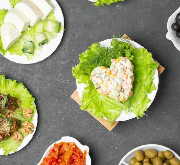 Русский столичный салат в форме сердца на листе салата. вид сверху