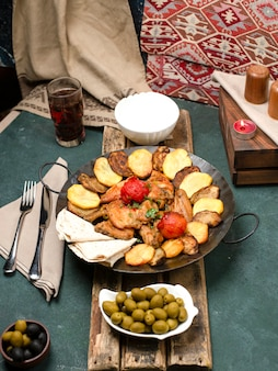 木の板にヨーグルトとコンポートを添えた肉とジャガイモの白人の嚢