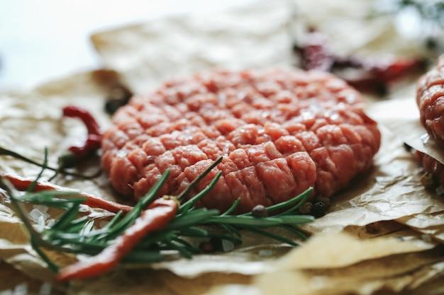 Сырые говяжьи гамбургеры с травами и специями на темной грифельной тарелке