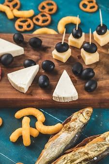 魚の燻製と木製のテーブルのチーズクラッカー