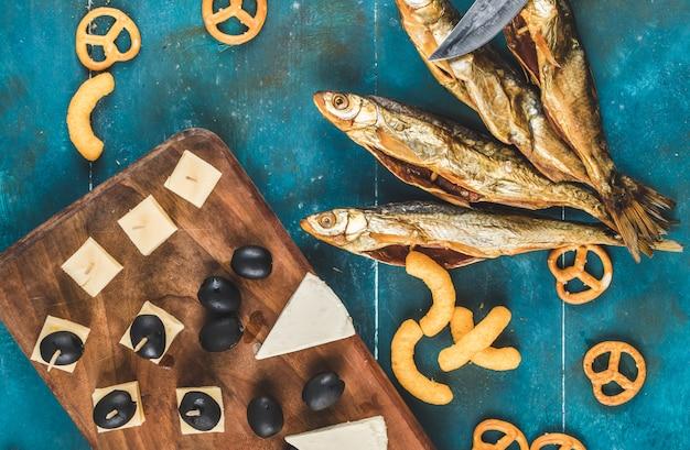 木の板の上の青いテーブルにチーズ、オリーブ、クラッカーと魚のスナックを乾燥します。