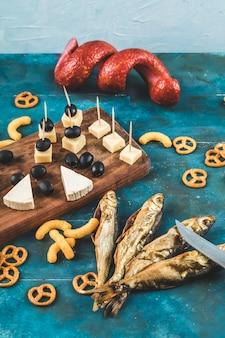 Ломтики колбасы с кубиками сыра, маслинами и крекерами на деревянной доске с сухой рыбой