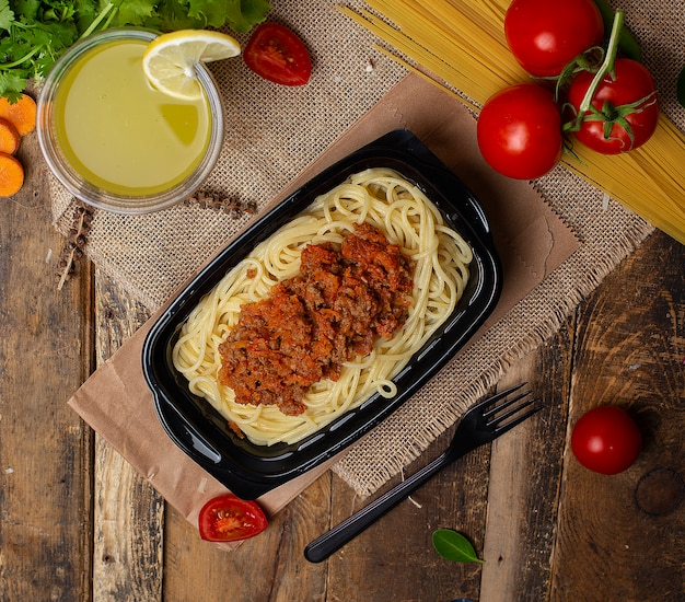 Спагетти с соусом из говядины и мясом в черной сковороде