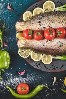 Сырые морепродукты с помидорами и лимоном на синем столе