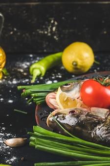 Сырые рыбные головы с зеленью, лимоном и помидорами