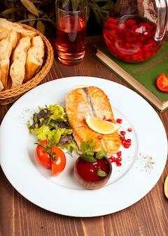 Филе рыбы белого лосося на гриле с зеленым салатом, помидорами, лимоном и соусом из красного дипа в белой тарелке