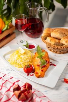 バジル、トマト、ライスを添えたサーモンフィッシュの切り身のグリル。